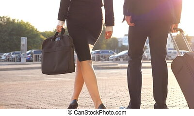 Business people leave airport and walking with their luggage at city street. Unrecognizable man and woman in heels stepping from terminal and roll suitcase on wheels. Concept of work trip. Slow motion
