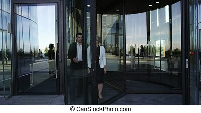 Business people leaving building - Two business people...