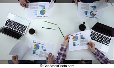 Business people list through graphs, top view