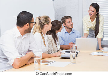Business people listening a woman doing a presentation in...