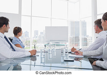 Business people looking at a blank whiteboard