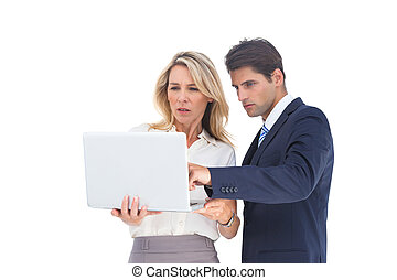 Business people looking at a laptop