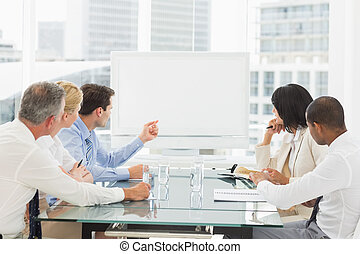 Business people looking at blank whiteboard in conference...