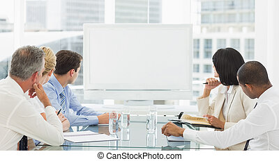Business people looking at blank whiteboard in the office