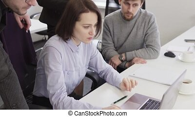 Business people looking at laptop screen during creative meeting at workplace