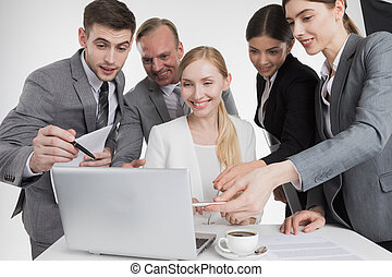 Business people looking at laptop screen