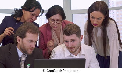 Business people looking at the laptop