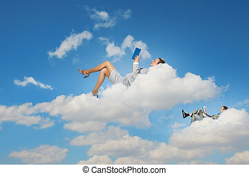 Business people lying on clouds