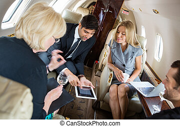 Business People Meeting In Private Jet - Businessman showing...