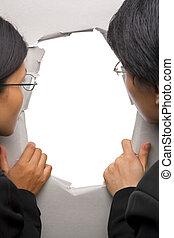 Business people peeking through hole in wall