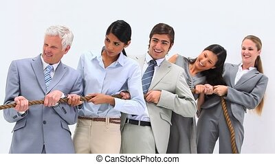 Business people playing Tug-of-War against a white...