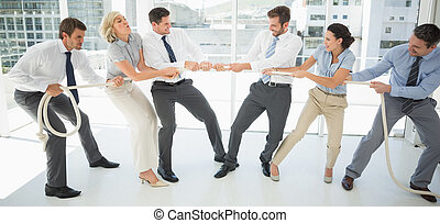 Business people playing tug of war in office - Full length...