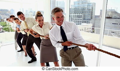 Business people pulling a rope together with motivation in the office