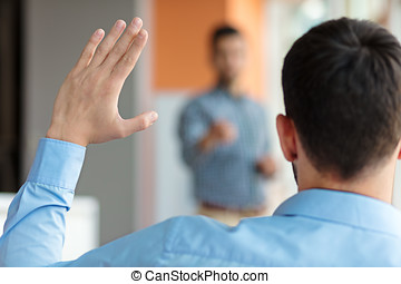 Business people Raising there Hand Up at a Conference to answer a question