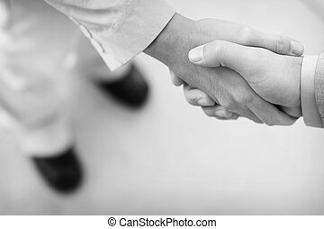 business people shake hands - two businessmen standing...