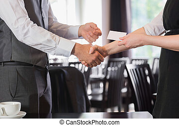 Business people shaking hands after meeting and changing cards
