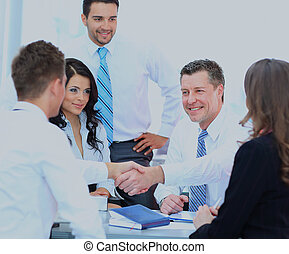 Business people shaking hands at a meeting.