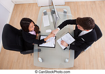 Business People Shaking Hands At Desk