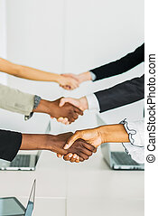 Business people shaking hands at the same time