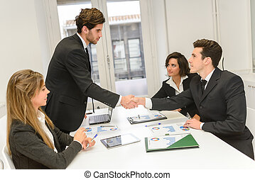 Business people shaking hands, finishing up a meeting - Four...