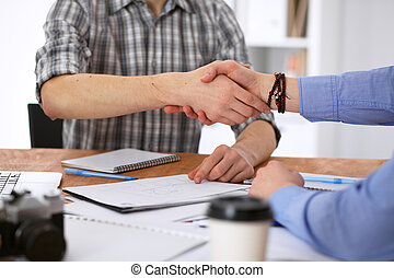 Business people shaking hands in office of hipster interiors.