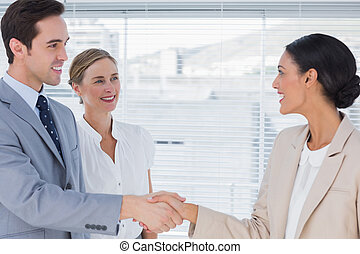 Business people shaking hands in the office with boss...