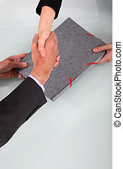 Business people shaking hands over a folder