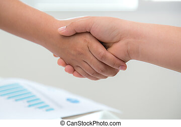 Business people shaking hands over business document