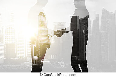 business people shaking hands over city background -...