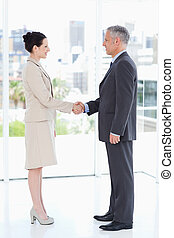 Business people shaking hands while smiling and looking at...