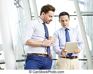 business people sharing information - two caucasian business...