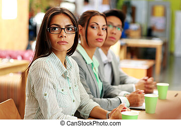Business people sitting around a table during a meeting in...