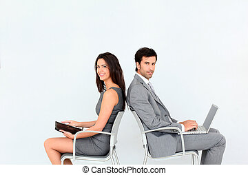 Business people sitting in chairs back to back