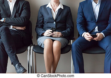 Business people sitting in chairs in queue waiting job interview
