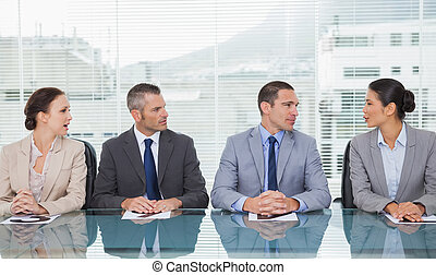 Business people sitting straight talking together in bright ...