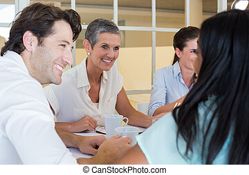 Business people smile and chat while enjoying hot drinks