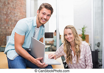 Business people smiling and working together with a laptop