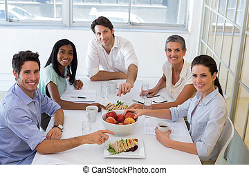 Business people smiling at camera eating sandwiches and fruit for lunch in the office