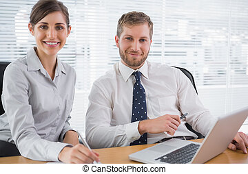 Business people smiling at camera with laptop