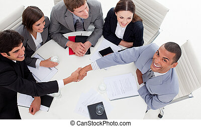 Business people smiling at the camera while closing a deal