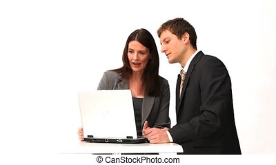 Business people speaking in front of a laptop isolated on a white background