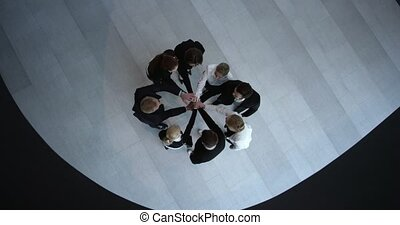 Business people stacking hands, teamwork, togetherness and...