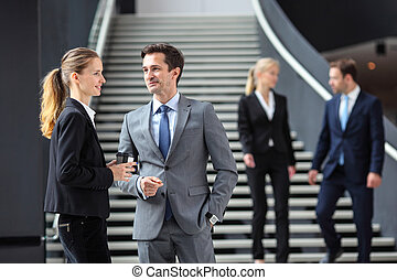 Business people standing in office lobby