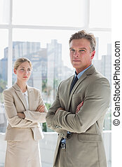Business people standing with arms