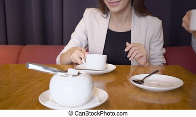 Business people talk and drink coffee while sitting in restaurant.