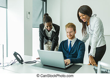 Business people talking and smiling in an office in front of a laptop