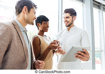 Business people talking and using tablet together in office