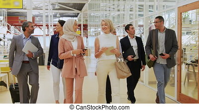 Business people talking and walking in a conference foyer