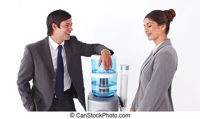 Business people talking next to the water cooler against a...