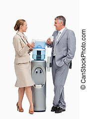 Business people talking next to the water dispenser against ...
